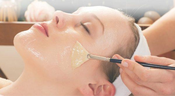 Девушке наносят маску на лицо с помощью кисти